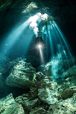 Male diver diving in underground river (cenote) with sun rays and rock formations, Tulum, Quintana Roo, Mexico - p429m1569467 by Rodrigo Friscione
