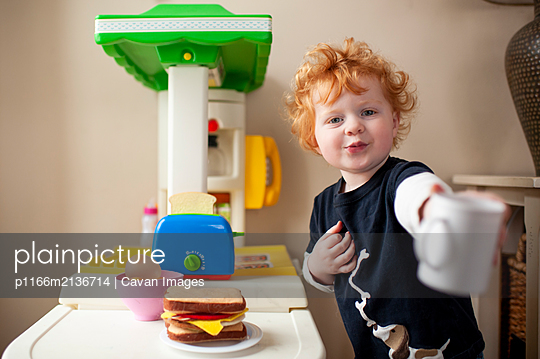 Toddler boy offering a cup of coffee in front of his play kitchen - p1166m2136714 by Cavan Images