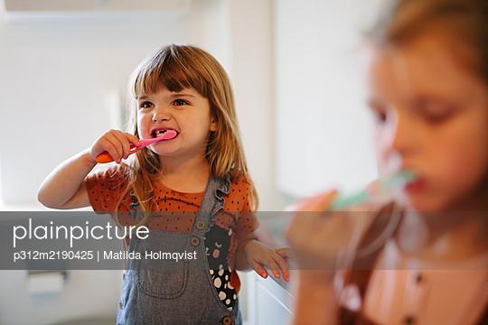 Girl brushing teeth - p312m2190425 by Matilda Holmqvist