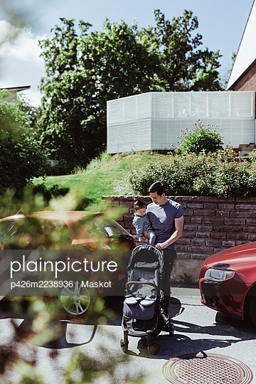 Father with baby stroller carrying male toddler on road during sunny day - p426m2238936 by Maskot