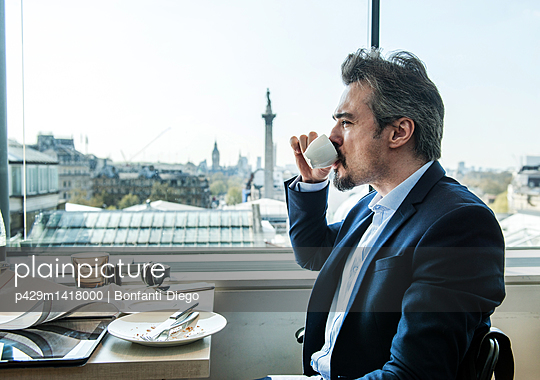 Businessman drinking coffee by restaurant window with rooftops views, London, UK - p429m1418000 by Bonfanti Diego