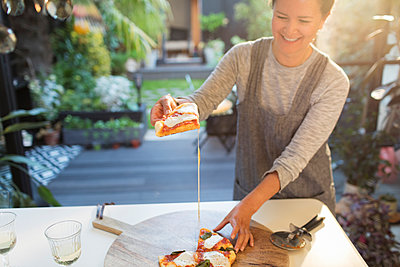 Smiling woman eating homemade pizza on patio - p1023m2208339 by Sam Edwards