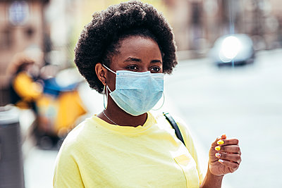 Portrait of black girl with face mask and afro hair waiting in an old city street. - p1166m2269358 by Cavan Images