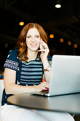 Smiling mid adult woman using smart phone and laptop - p1427m2128252 by Jessica Peterson