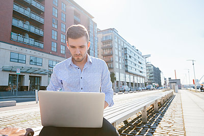 Young businessman sitting on bench using laptop - p300m1175720 by Boy photography