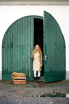 Woman on a farm standing at crate with apples - p300m1562393 by Peter Scholl