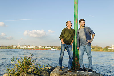 Smiling son and father leaning by pole while looking away at riverbank against sky - p300m2252614 by Gustafsson