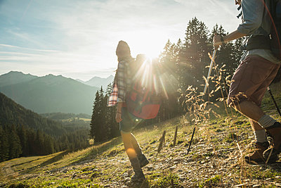 Austria, Tyrol, Tannheimer Tal, young couple hiking in sunlight on alpine meadow - p300m979075f by Uwe Umstätter