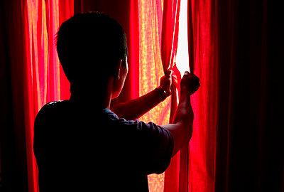 Man peeks through curtains - p4421985f by Design Pics