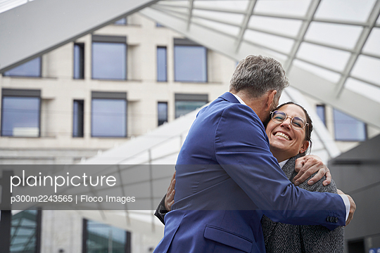 Senior businessman hugging cheerful businesswoman while greeting in city - p300m2243565 by Floco Images