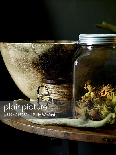 Dried courgette flowers with ceramic bowl and spool of string with scissors - p349m2167824 by Polly Wreford