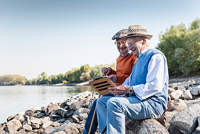 Two old friends sitting by the riverside, using digital tablet - p300m2062890 by Uwe Umstätter