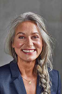 Happy businesswoman with gray hair against wall at home office - p300m2241302 by Maya Claussen