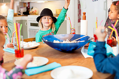 Girls raising hands by table - p312m1164754 by Rebecca Wallin