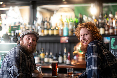 Two male customers looking over their shoulders from bar in traditional Irish public house - p429m2069257 by Sigrid Gombert