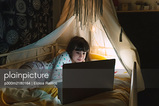 Portrait of girl lying on bed at night looking at laptop - p300m2180164 by Eloisa Ramos