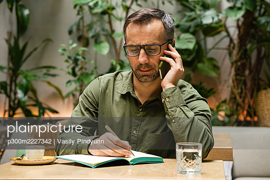 Businessman wearing eyeglasses writing in book while talking on mobile phone at cafe - p300m2227342 by Vasily Pindyurin