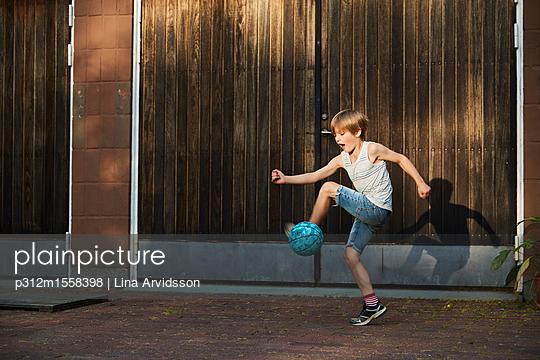 plainpicture - plainpicture p312m1558398 - Boy kicking ball - plainpicture/Johner/Lina Arvidsson