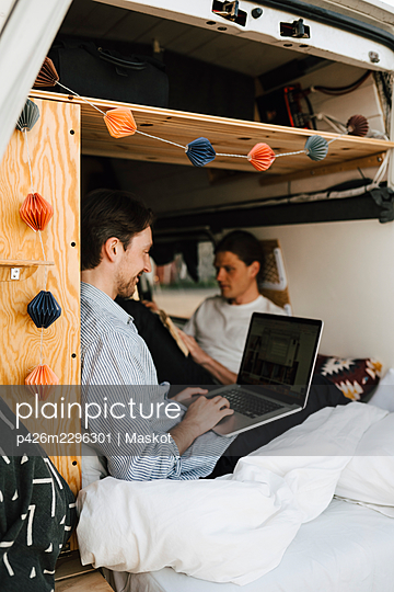 Man using laptop sitting with boyfriend in motor home - p426m2296301 by Maskot