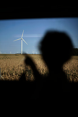 Young boy looking at wind turbines from the train, Beauce, France - p1028m2007757 von Jean Marmeisse