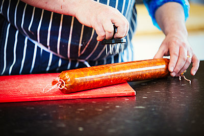 Close up of a butcher wearing a striped blue apron, pricking holes into the casing of a Chorizo sausage. - p1100m1178315 by Mint Images