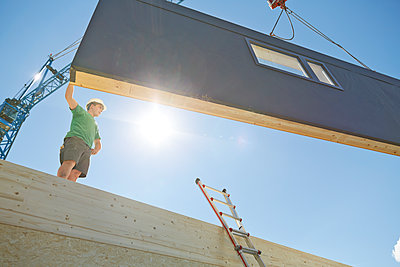 Austria, worker against the sun, positioning exterior wall - p300m1567836 by Christian Vorhofer