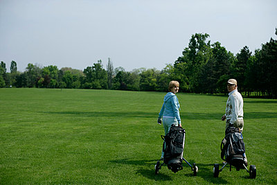 Ein Mann und eine Frau gehen mit Golfcaddy über einen Golfplatz, Blick über die Schulter - p4902231 von Stock4B