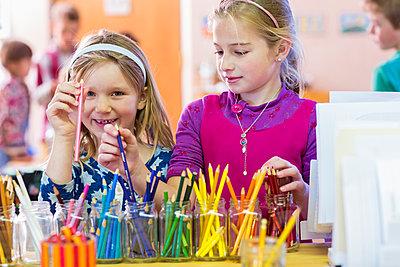 Caucasian girls choosing multicolor pencils in classroom - p555m1410219 by Marc Romanelli