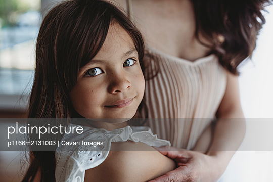 Close up view of school aged girl being hugged by mother - p1166m2131003 by Cavan Images