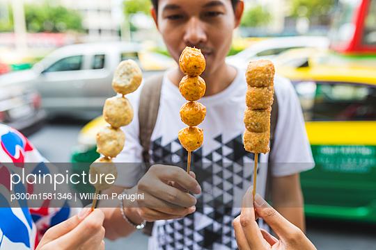 Thailand, Bangkok, group of friends eating street food, close-up - p300m1581346 von William Perugini