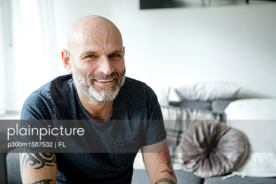 Tattooed man at home sitting on couch - p300m1587532 von FL photography