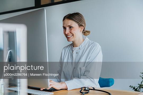 Doctor working on computer at desk - p300m2286764 von Mareen Fischinger
