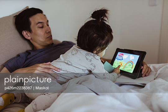 Male toddler watching cartoon on digital tablet with father in bedroom - p426m2238387 by Maskot