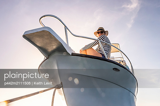 A woman wearing sunglasses and a sun hat looks down at the camera from the deck of a boat against a blue sky with sunlight; Bay Islands Department, Honduras - p442m2111508 by Keith Levit