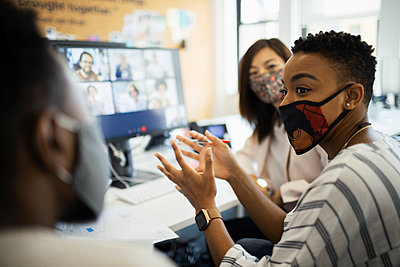 Business people in face masks video conferencing at computer in office - p1023m2261556 by Paul Bradbury