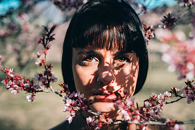 Woman In Behind Cherry Blossom Tree - p1166m2233257 by Cavan Images