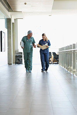 Surgeon and nurse discussing medical record, walking in hospital corridor - p1192m1493379 by Hero Images