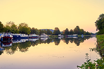 Moored houseboats in a canal at sunset - p1312m2269995 by Axel Killian