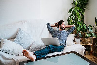Man with hands behind head sitting with laptop on sofa at home - p300m2242349 by Eva Blanco