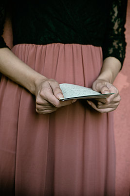 Close up of young woman holding a letter  - p794m2135050 by Mohamad Itani