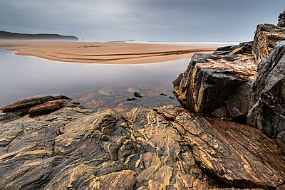 Rock formations at Sandwood Bay, with Am Buachaille sea stack in far distance, Sutherland, Scotland, United Kingdom - p871m2111546 by Bill Ward
