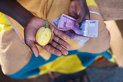 Africa, Uganda, African woman with bank note - p1167m2283466 by Maria Schiffer