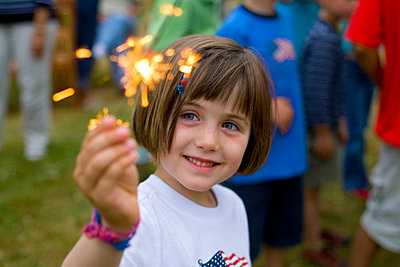 A young girl holds a sparkler at a party in North Yarmouth - p3433763 by David McLain