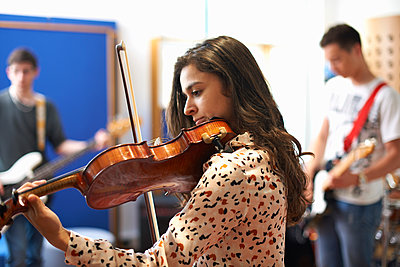 Young female college student playing violin in recording studio - p429m1494621 by Peter Muller