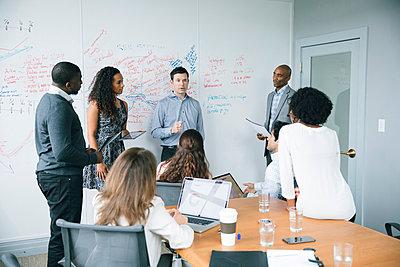 Businessman talking near whiteboard in meeting - p555m1504095 by John Fedele