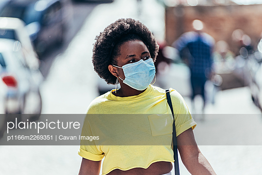 Black girl with face mask and afro hair walking through the city. - p1166m2269351 by Cavan Images