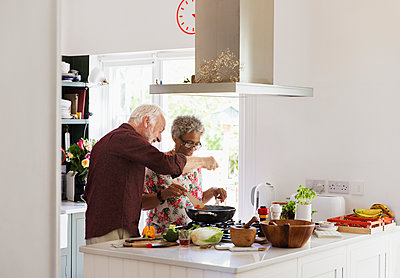 Active senior couple cooking in kitchen - p1023m2024374 by Tom Merton