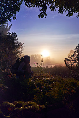 Silhouette affectionate young couple enjoying scenic sunset in nature - p1023m2212902 by Trevor Adeline