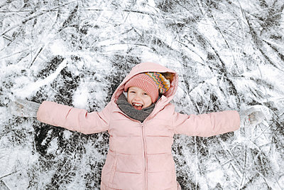 Portrait of happy girl with arms outstretched lying on ice - p300m2160106 by Ekaterina Yakunina