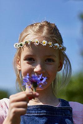 Portrait of girl wearing daisy wreath holding a flower - p300m2198601 by Maya Claussen